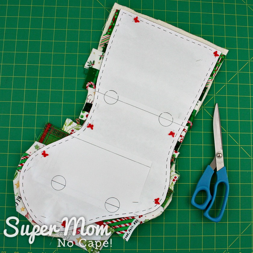 Paper pattern pinned to quilted stocking base ready to be cut out.