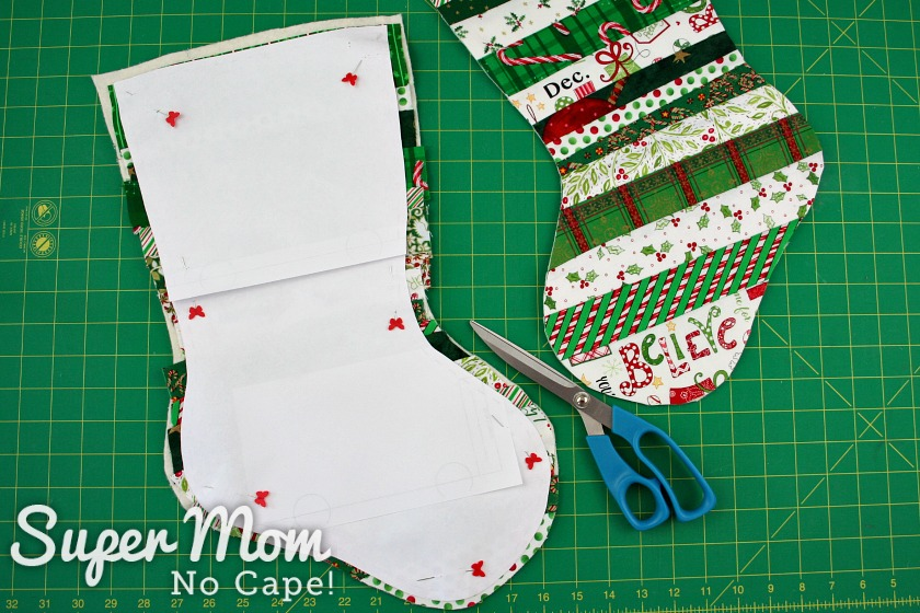 Paper pattern pinned to second quilted stocking base with the cut out one laying beside it and a pair of blue handled scissors.