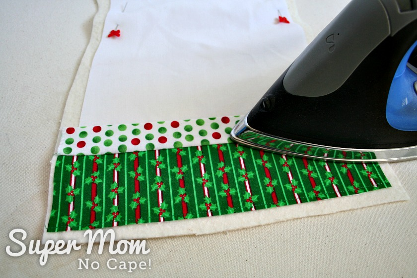 An iron pressing the second strip of fabric down