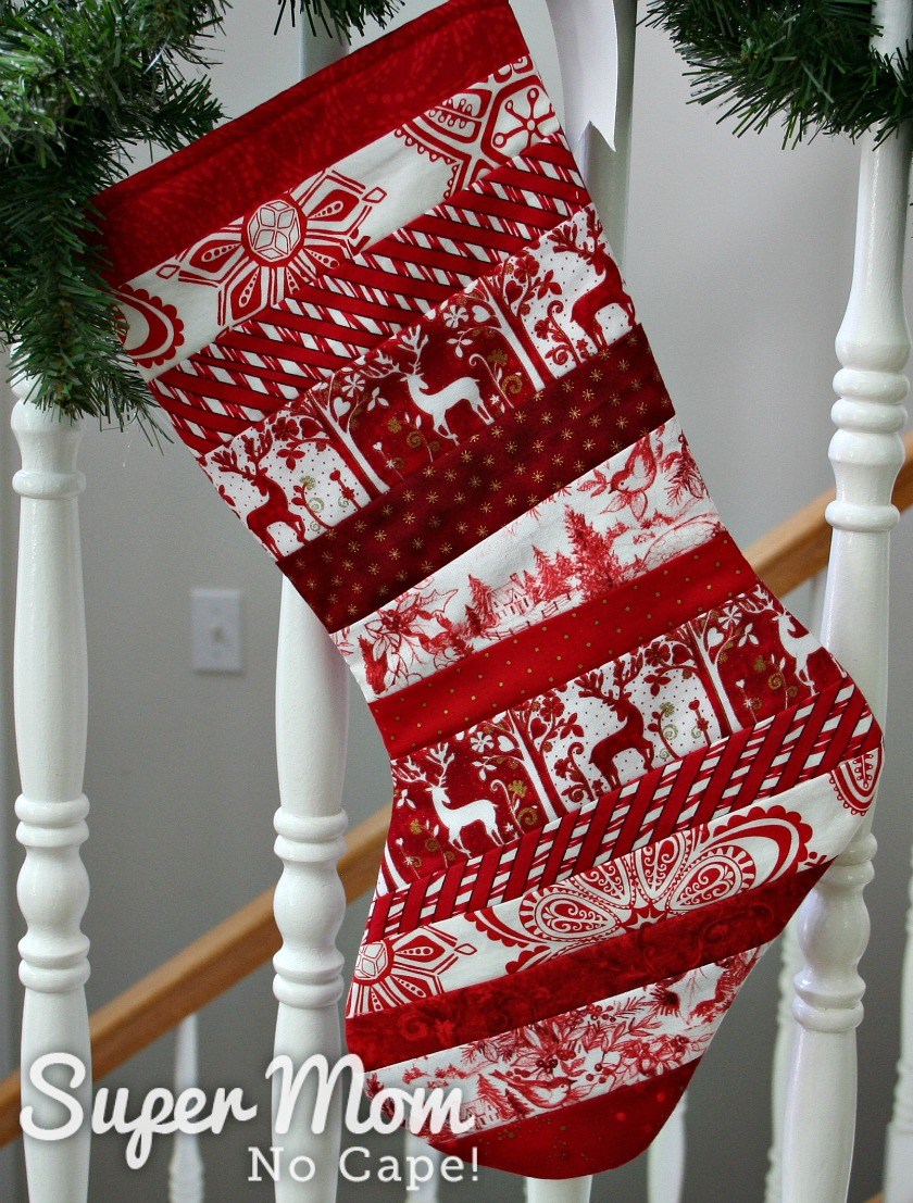 Red Quilt as you go stocking with toe facing left hung on stair railing wrapped with pine garland.