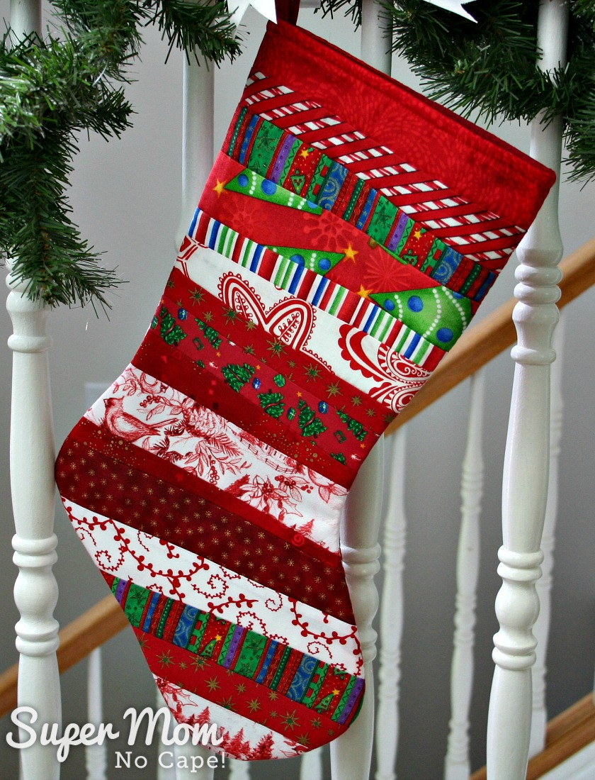 Red quilt as you go stocking with toe facing right tied to a stair railing wrapped in pine branches.