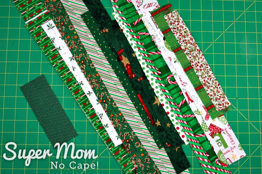 Several strips of a variety of Christmas print fabric lined up on a green cutting mat