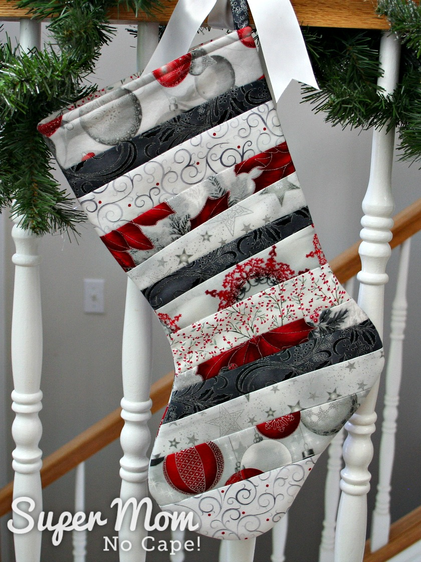 Silver and red QAYG stocking with toe facing left hung on a banister wrapped in pine boughs.