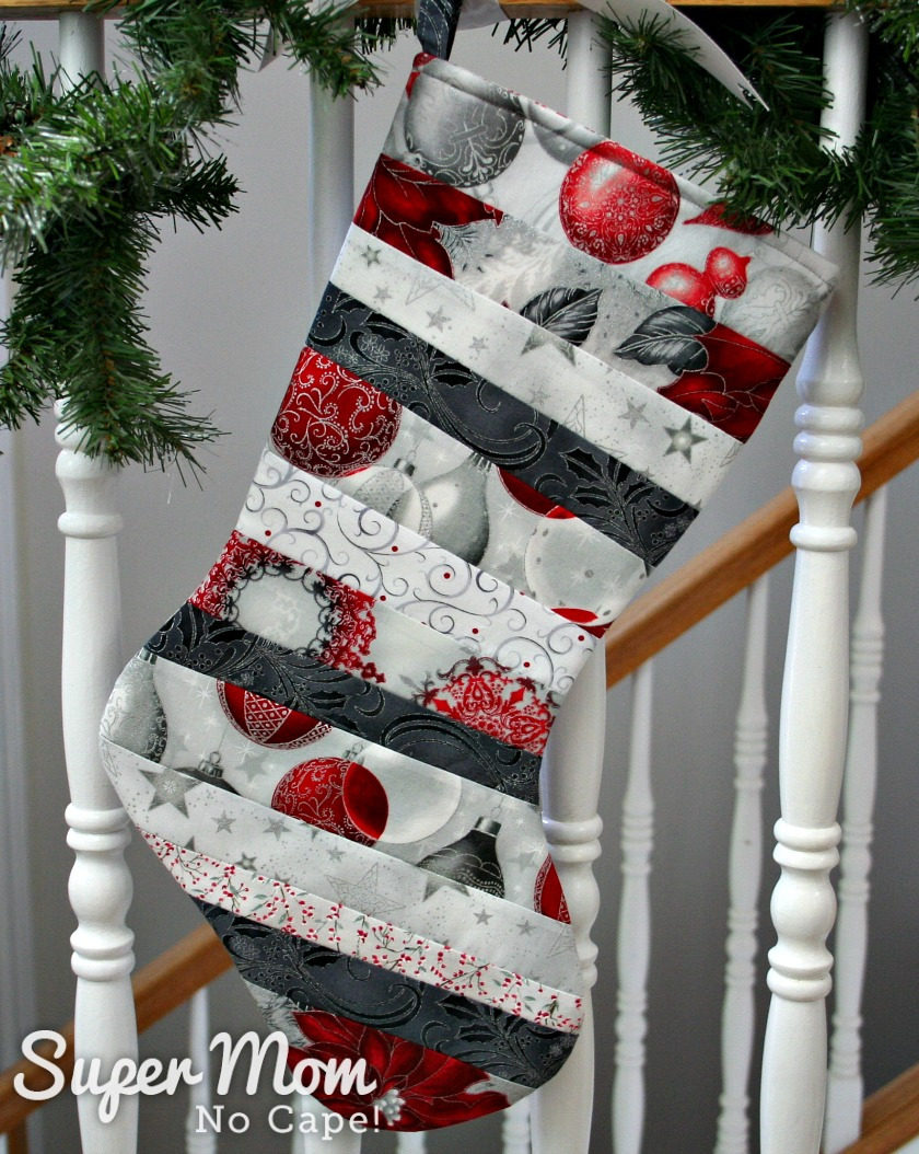 Silver and red quilt as you go stocking with toe facing right hung on stair railing wrapped with pine branches.