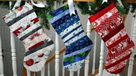 Three quilt as you go stockings hung on a handrail wrapped with pine branches