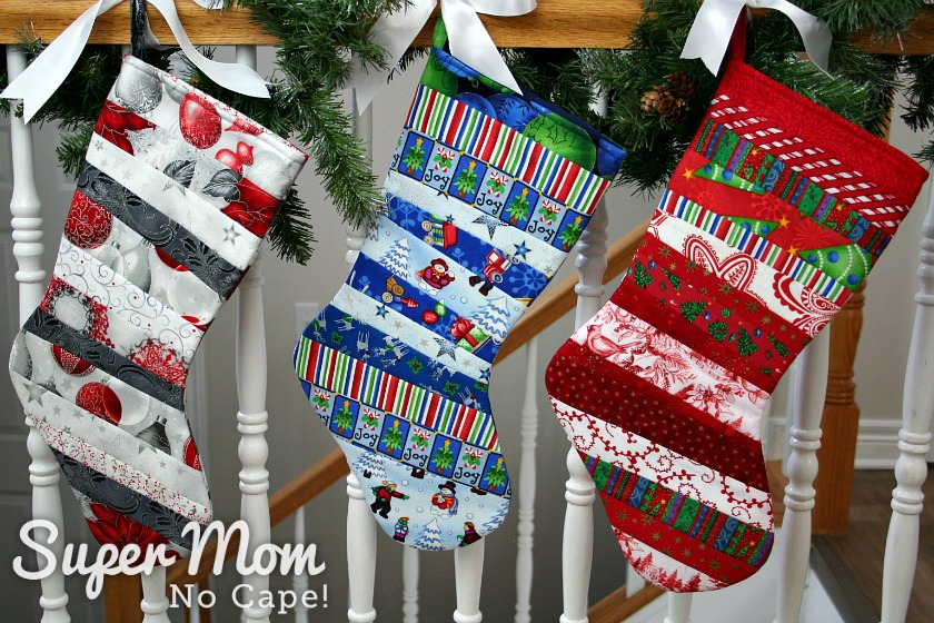 Three quilt as you go stocking in various colored fabrics hung on a bannister wrapping in pine boughs.