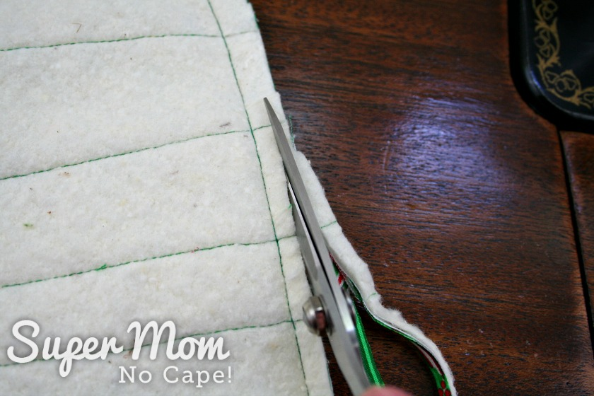 A pair of scissors trimming excess seam allowance from quilted stocking