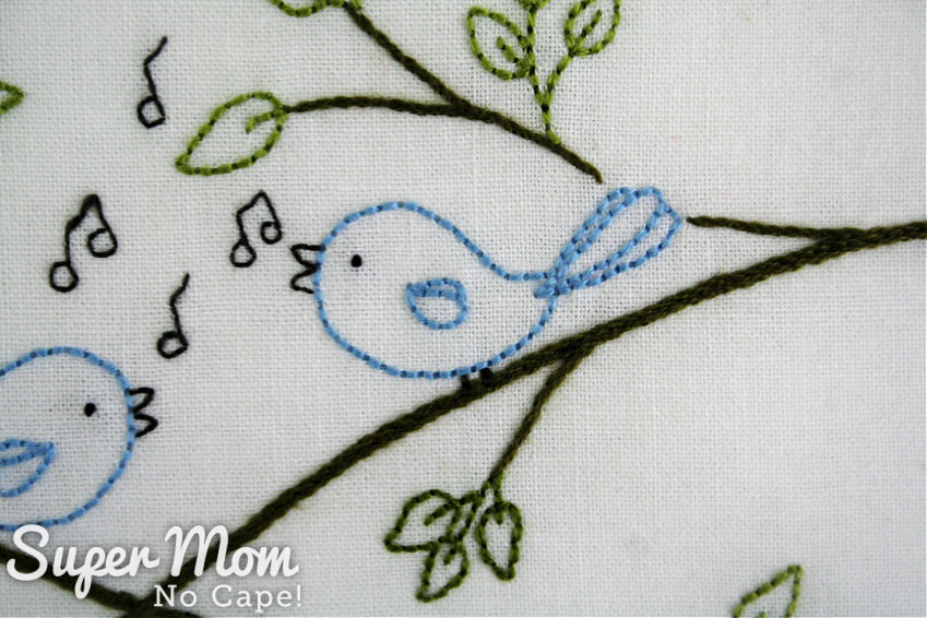 Close up of one of the songbirds stitched in blue embroidery floss.