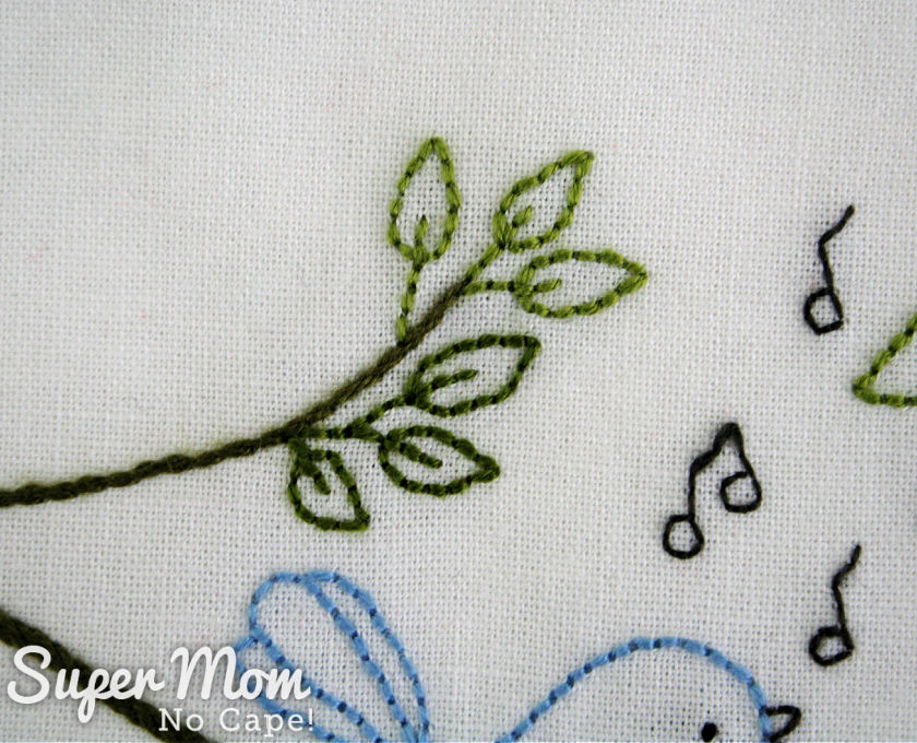 Closeup of embroidered leaves on the upper branches of the Song Birds embroidery.