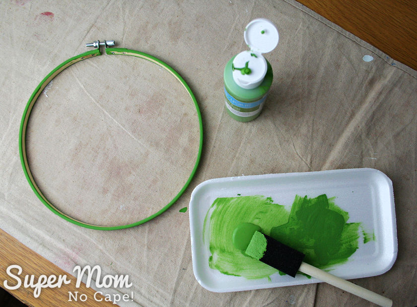 Outer embroidery hoop being painted green.