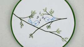 The Songbirds pattern framed in an embroidery hoop painted green.