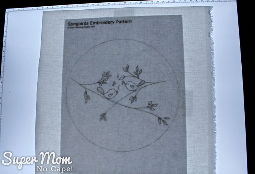 White square of fabric placed over the printout of the Songbirds Embroidery Pattern on a lightbox.