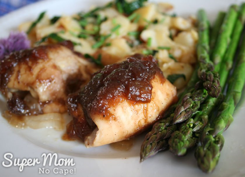 2 cooked chicken thighs on a plate with asparagus and fried sliced potatoes.