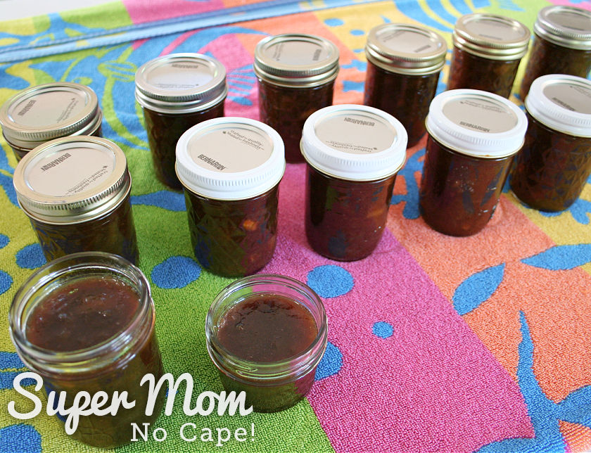 11 sealed half pint jars of rhubarb relish, 1 open half pint and one open quarter pint jar cooling on a colorful towel.