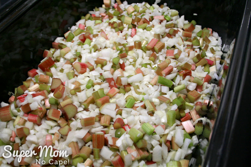 Chopped onions and rhubarb in a black roaster pan.