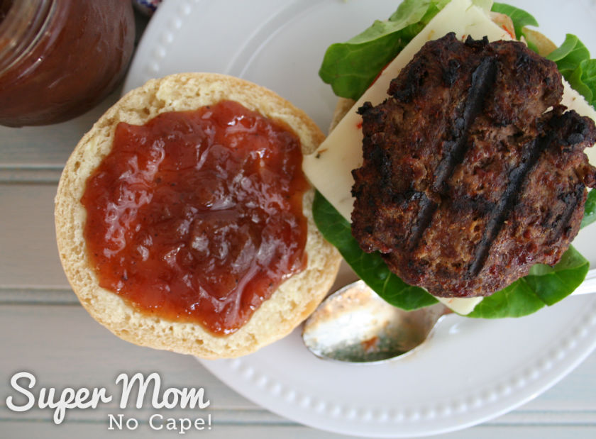 Rhubarb relish spread on the top of a homemade roll beside a grilled burger over cheese and lettuce.