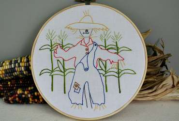 Photo of the Strawbyn Scarecrow Embroidery Pattern in a wooden hoop