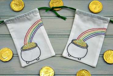 Two small drawstring bags with pot of gold embroidery